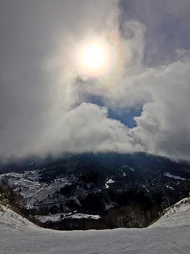 雪山の初日の出で太陽に虹